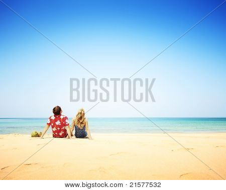 Young happy couple sitting on yellow sand by blue sea and looking to a clear sky