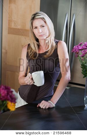 Woman With Mug In Kitchen