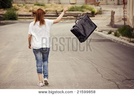 Young Girl Throws Her Suitcase Walking Down The Street