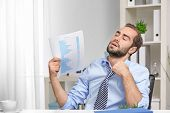 Young man feeling hot in office poster