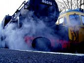 foto of bowser  - A low view of an old steam engine next to a diesel engine - JPG