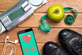 Sports Shoes , Apple , Scales, And A Phone With Health Card On A Wooden Background. Mobile App Healt poster