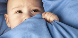 stock photo of fussy  - afraid baby under a blue blanket closeup - JPG