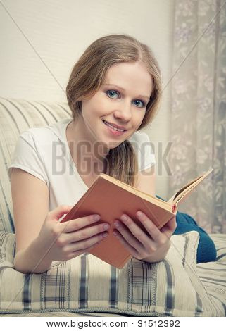 Pretty Girl Reading A Book Lying On The Sofa