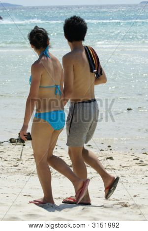 Young Couple Walking On The Beach.