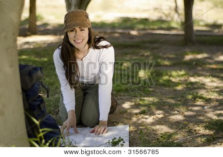 Young woman looking at map on a hiking trip