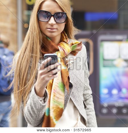 Young Fashionable Woman With Smartphone Walking On Street