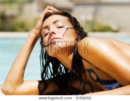 Beautiful Young Woman Basking In The Warm Sunshine Beside A Swimming Pool.