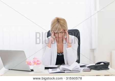 Stressed Middle Age Business Woman Sitting At Office Table