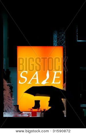 Silhouette Of A Passerby On Storefront With Sale Inscription