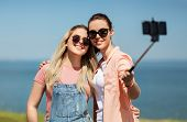 leisure and friendship concept - happy smiling teenage girls or best friends in sunglasses hugging a poster