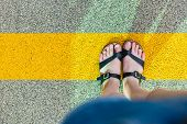 Womens Feet In Slippers Standing At The Yellow Line On Asphalt. Personal Perspective Of Person Looki poster