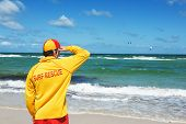 stock photo of dangerous situation  - young man life saver watching the situation on the sea - JPG