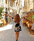 Woman In Beautiful Flowered Dress Walking With Open Arms In Street Of Syracuse, Sicily. Rear View Of poster