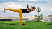 Young Woman With Trim Figure Practicing Yoga Warrior Pose. Girl Performs Yoga In A Park On Internati poster