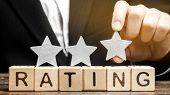 Businessman Puts The Third Star Above The Word Rating On Wooden Blocks. The Concept Of Quality Of Se poster