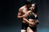 Shirtless Man Hugging Sexy And Wet Girl Under Raindrops On Black poster