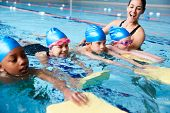 Female Coach In Water Giving Group Of Children Swimming Lesson In Indoor Pool poster