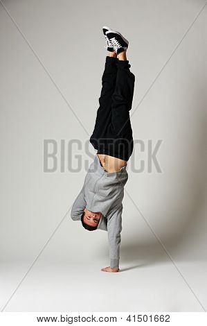 full length portrait of cool b-boy on one hand over grey background