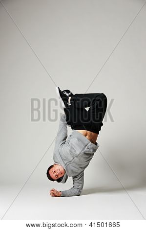 breakdancer standing on his elbow over grey background
