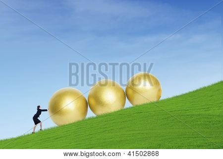 Businesswoman Push Golden Eggs On Hill