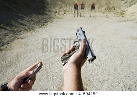 Close up of man's hand reloading gun