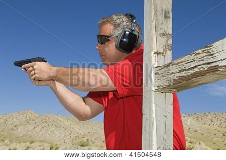 Mature man aiming with handgun at combat training