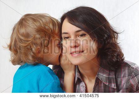 Little blond boy whispers secrets to his mother