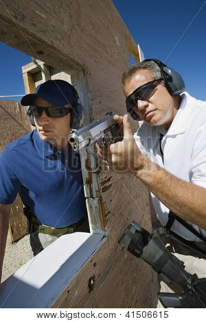 Trainer standing with mature man aiming with gun