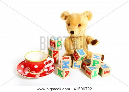 Teddy Bear, Cup, Plate And Box Of Bricks Isolated On White