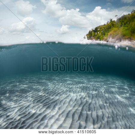 Underwater shoot of a sandy sea bottom and green tropical island with cloudy sky above sea surface