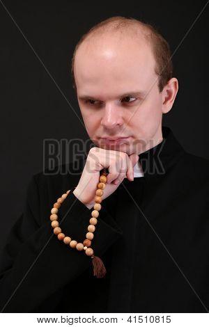 Jovem pastor com Rosário de madeira, isolado em preto