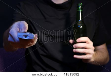 Man hand holding a TV remote control and beer bottle, on dark background