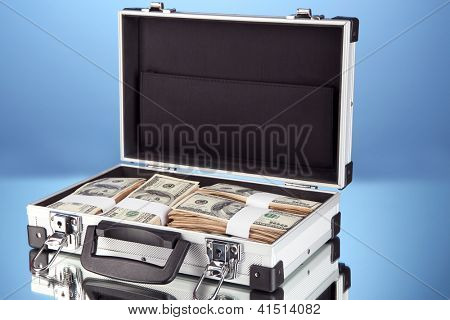 Suitcase with 100 dollar bills on blue background