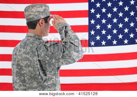 Closeup of a young American Soldier in Fatigues saluting the Flag. Flag fills the frame and is out of focus. Man is seen from behind.