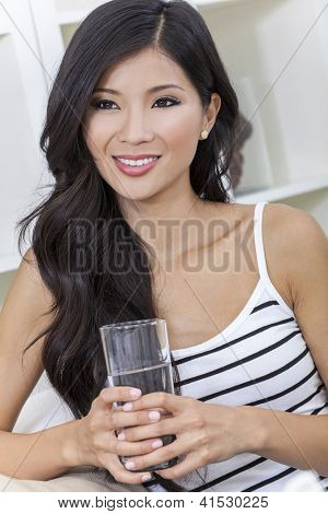 A beautiful happy young Chinese Asian Oriental woman with a wonderful toothy smile drinking a glass of water at home