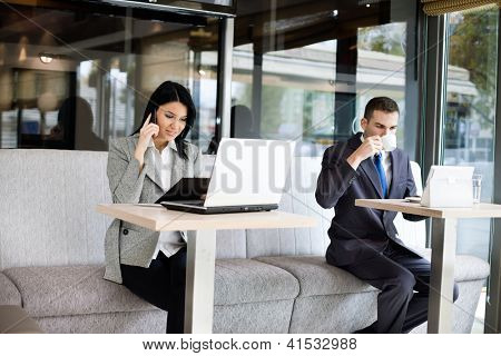 Busy business people in cafe, working while break