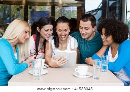 group of teenagers in cafe  using digital tablet