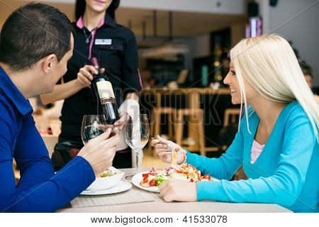 Young couple having lunch in restaurant and choosing wine