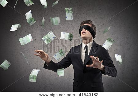 Blindfolded businessman trying to catch a hundred-euro banknotes flying in the air