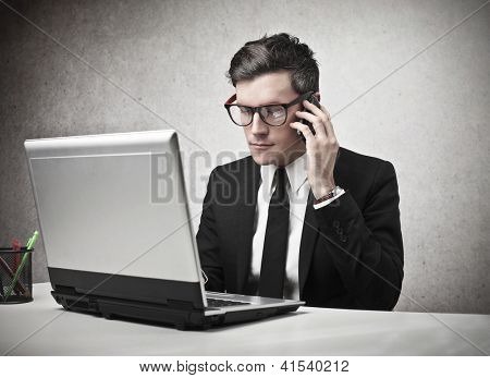 Serious businessman calling someone with a mobile phone while is using a laptop