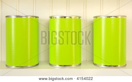 Three Metal Cans On A Shelf