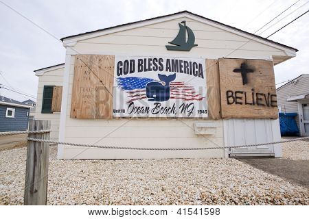 OCEAN BEACH, NJ - JAN 13: A banner that says God Bless America hangs next to a cross and word 'Believe' spray painted on a home on January 13, 2013 in Ocean Beach, NJ. Hurricane Sandy hit in Oct 2012.