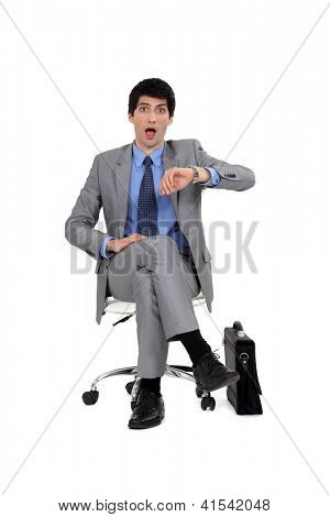 Shocked businessman looking at the time
