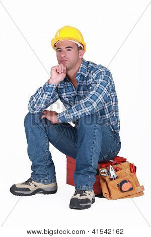 tradesman sitting on toolchest isolated on white
