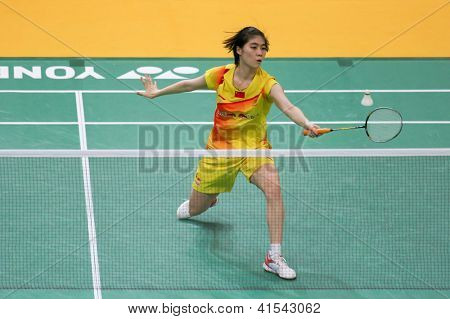 KUALA LUMPUR - JANUARY 15: China's Xuan Deng retrieves the shuttlecock during her qualifying match at the Maybank Malaysia Open 2013 Badminton event on January 15, 2013 in Kuala Lumpur, Malaysia.