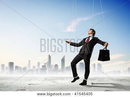 Image of businessman hanging on strings like marionette against city background. Conceptual photography