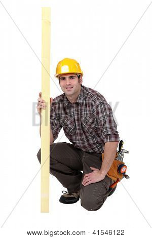 Carpenter holding a plank of wood