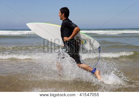 Surfer running with board