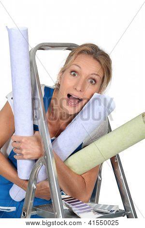 Happy woman with rolls of wallpaper